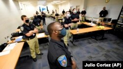 In this Sept. 9, 2020 photo, training police officers at the Baltimore Police Academy watch a video presentation during a class session on justice in Baltimore. (AP Photo/Julio Cortez)