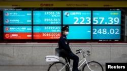 一名戴着口罩的日本警察骑车停站在东京街头一个日经指数电子显示板前。(路透社2020年2月26日资料照)