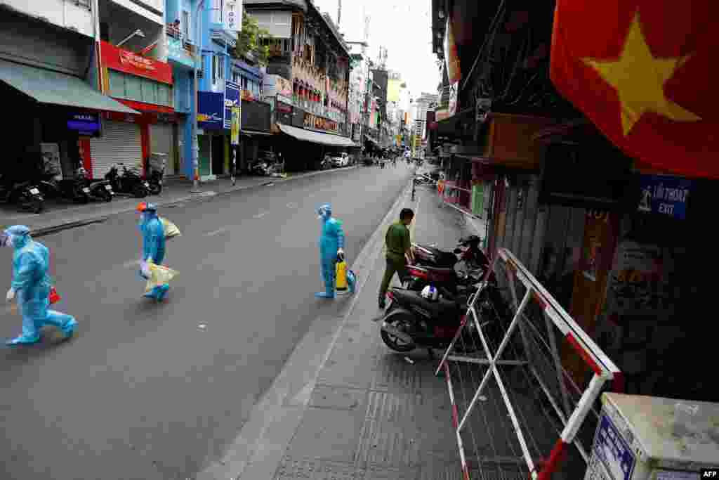 Medical workers collecting test samples from residents walk through Ho Chi Minh City on the first day of the government imposed two-week lockdown as a preventive measure to stop the spread of COVID-19.