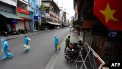 Nhân viên y tế đi lấy mẫu xét nghiệm COVID-19 ở thành phố Hồ Chí Minh (ảnh tư liệu, 9/7/2021).