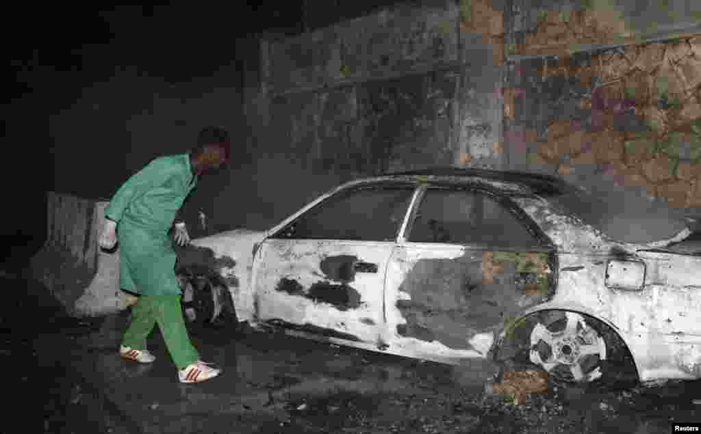 A firefighter looks at a destroyed car at the scene of an explosion outside the Jazeera Hotel in Mogadishu, Jan. 1, 2014.