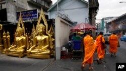 Tiga Bhiksu Budha tengah berjalan melewati toko yang menjual patung-patung Budha di Bangkok, Thailand, 15 Desember 2013 (Foto: dok). Seorang bhiksu dan tiga orang lainnya tewas ditembak serombongan orang-orang tak dikenal di di daerah Mae Lan, provinsi Pattani, Kamis pgi (13/2).