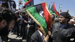 An unidentified African Union delegation official has an opposition flag draped over him as he arrives for meetings with opposition leaders in Benghazi, Libya Monday, April 11, 2011.
