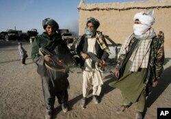FILE - Taliban militants stand beside the burnt trucks, background left, on main Ghazni- Kandahar highway in Ghazni, west of Kabul, Afghanistan, Oct.19, 2009.