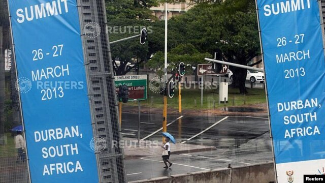 A woman walks past the International Convention Center where the 5th BRICS Summit will be held, in Durban, South Africa, Mar. 25, 2013.