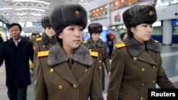 Members of the Moranbong Band of North Korea arrive at Beijing International Airport before departing from Beijing, China, on Dec. 12, 2015.