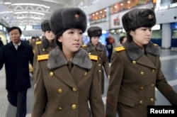 Members of the Moranbong Band of North Korea arrive at Beijing International Airport before departing from Beijing, China, Dec. 12, 2015.