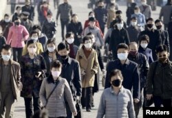 Orang-orang di Pyongyang, ibu kota Korea Utara, memakai masker di tengah pandemi COVID-19, 30 Maret 2020. (Kyodo News/Reuters)