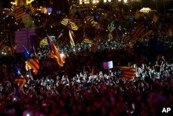 人们在西班牙巴塞罗那街头游行,手中挥舞着加泰罗尼亚旗帜