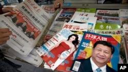 北京报摊上的报纸刊物,其中《环球人物》杂志的封面上有习近平照片和《习近平 中国强起来》的标题,还有报道中共十九大修改党章消息的北京晚报,也有以影视明星范冰冰为封面的《知音》杂志。(2017年10月21日)