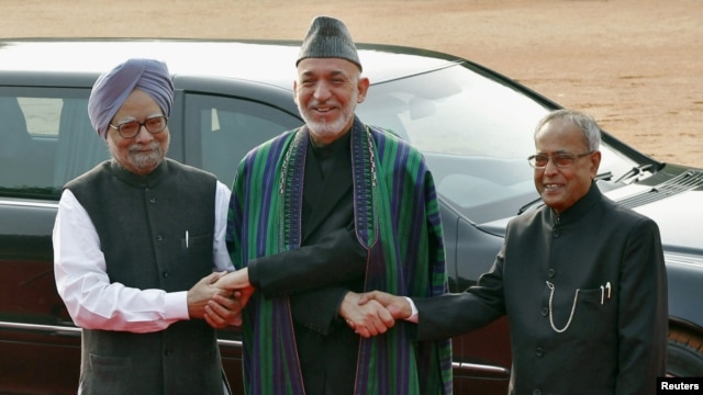 Afghanistan's President Hamid Karzai (C) shakes hands with his Indian counterpart Pranab Mukherjee (R) and Indian PM Manmohan Singh during a ceremonial reception in New Delhi, November 12, 2012.
