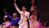 """Performers from the musical Aladdin give a """"curtain call"""" after a performance in New York City on Sept. 28, 2021. From second left, Michael James Scott as Genie, Michael Maliakel as Aladdin, and Shoba Narayan as Jasmine. (Photo Courtesy of Disney Theatrical Productions)"""