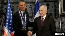 President Barack Obama shakes hands with Israeli President Shimon Peres after Peres presented him with the Israeli Medal of Distinction at a state dinner in Jerusalem on March 21, 2013.