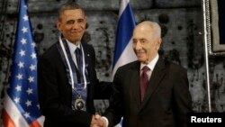 FILE - President Barack Obama shakes hands with Israeli President Shimon Peres after Peres presented him the Israeli Medal of Distinction in Jerusalem, Israel, March 21, 2013.