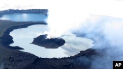 FILE - This Sunday, Oct. 1, 2017 photo provided by GeoHazards Divison, Vanuatu Meteorological and GeoHazards Department, shows an aerial view of the volcanic cone that has formed in Lake Vui near the summit of Ambae Island, Vanuatu. (Brad Scott/GeoHazards Divison, VMGD via AP)