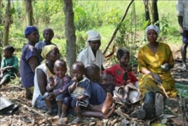 Women farmers take a break with their children in the village where they are part of a pioneering project to help control food production, as well as its distribution, and the use of the profits from their labor, in Naminya, Uganda, December 2011.
