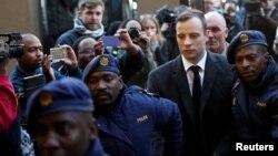 Pelari peraih medali emas Paralimpik, Oscar Pistorius dikawal oleh perwira polisi saat tiba untuk pembacaan hukuman yang akan diterimanya terkait kasus pembunuhan pacarnya, Reeva Steenkamp, di Pengadilan Tinggi Pretoria di Afrika Selatan, 6 Juli 2016. (Foto:dok)