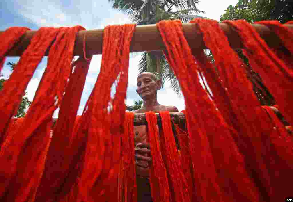 A worker hangs yarns to dry at a textile mill on the outskirts of Agartala, India.