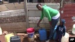 南非马卡乌斯社区居民在公共水龙头前用桶打水