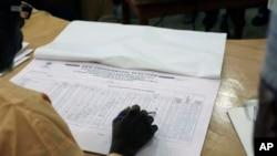 尼日利亚选举工作官员阅读地方投票结果。