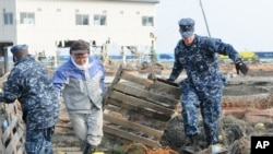 US sailors help remove debris during a cleanup effort at Japan's Misawa Fishing Port on March 14, 2011.
