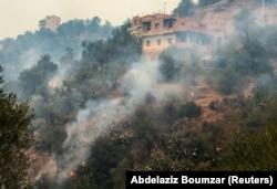 Asap mengepul dari kebakaran hutan di pegunungan Provinsi Tizi Ouzou, sebelah timur Ibu Kota Aljazair, Aljir, 10 Agustus 2021. (Foto: REUTERS/Abdelaziz Boumzar)