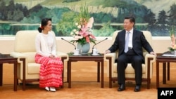 Chinese President Xi Jinping (R) meets Myanmar's pro-democracy leader Aung San Suu Kyi at the Great Hall of the People in Beijing on June 11, 2015.
