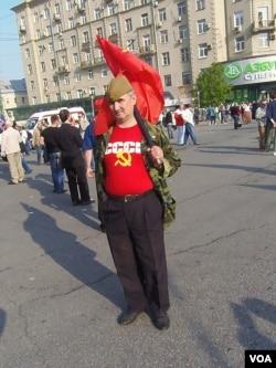 2012年5月普京再次就职总统前夕莫斯科爆发大规模反政府和反普京再次执政示威。一名示威者手举共产党红旗,身穿苏联标志服装表达他对苏联的怀恋。(美国之音白桦拍摄)