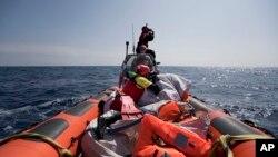 Une équipe de Proactiva Open Arms effectue une opération de recherche et de sauvetage de migrants en Méditerranée, à 12 milles nautiques de la côte libyenne, le jeudi 13 avril 2017.