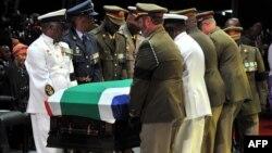 Cette image publiée par les services de communication du Gouvernement sud-africain montre des officiers portant le cercueil de Nelson Mandela lors de ses funérailles d'État, dimanche 15 décembre, 2013 à Qunu. (AFP/GCIS/Kopano Tlape)
