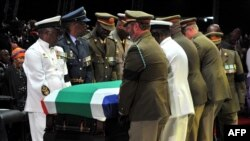 Petugas mengangkat peti mati Nelson Mandela dalam upacara pemakaman kenegaraan di Qunu, 15 Desember 2013.