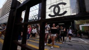 Shoppers walk across Canton Road, famous for its luxury brand stores, at Hong Kong's Tsim Sha Tsui shopping district, May 9, 2013.