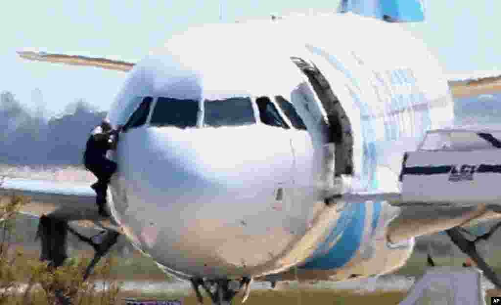 A man, leaves the hijacked aircraft of Egyptair from the pilot's window after landing at Larnaca airport in Cyprus. The plane was hijacked while flying from the Egyptian Mediterranean coastal city of Alexandria to the capital, Cairo, and later landed in Cyprus where some of the women and children were allowed to get off the aircraft, according to Egyptian and Cypriot officials. The hijacker was arrested later after hours of negotiations.