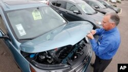 FILE - A sales manager at a Honda car dealership, opens the hood of a Honda CRV SUV, Dec. 2, 2014, in Tempe, Arizona.