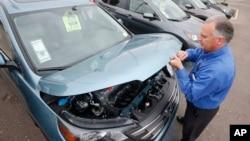 一名銷售經理打開一輛本田汽車的引擎蓋(2014年12月2日)