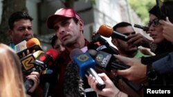 El líder opositor venezolanno, Henrique Capriles, (centro) habla con los periodistas después de emitir su voto durante las elecciones primarias de la oposición en Venezuela, el domingo, 10 de septiembre, de 2017.