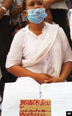 A woman, dressed in white, display documents from the land dispute.