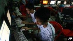 Dua pemuda Vietnam mengakses Facebook dari warnet dekat asrama mereka di Hanoi, Vietnam. (Foto: dok).