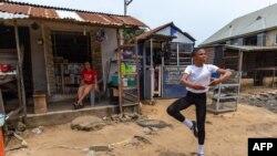 Un étudiant de la Leap of Dance Academy, Anthony Madu, effectue une routine de danse classique devant la boutique de sa mère dans la rue Okelola à Ajangbadi, Lagos, le 3 juillet 2020.