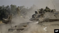 An Israeli tank drives next to the border between Israel and the southern Gaza Strip, April 8, 2011