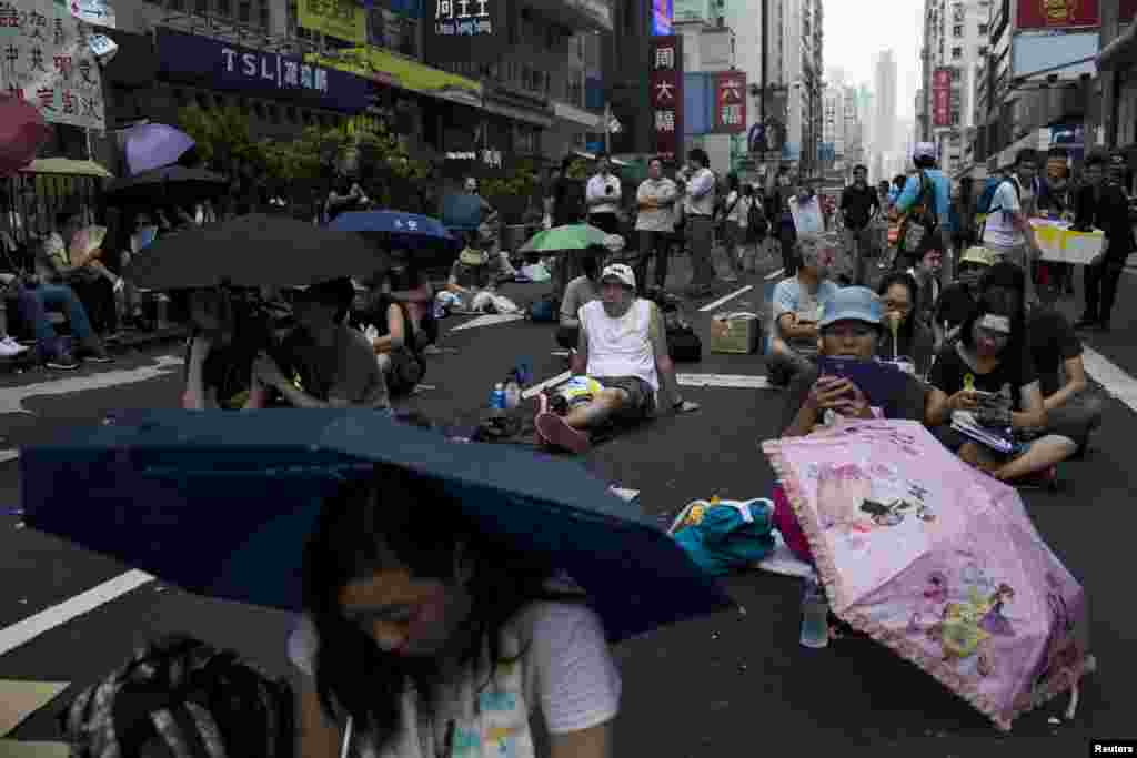 People sit under umbrellas as they attend a rally along a main street at Mongkok shopping district in Hong Kong, Sept. 30, 2014.