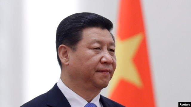 FILE - China's President Xi Jinping stands next to a Chinese national flag during a welcoming ceremony at the Great Hall of the People, in Beijing, Nov. 13, 2013.