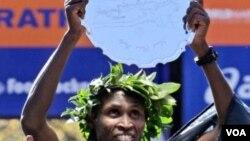 Geoffrey Mutai, dari Kenya, mengangkat penghargaannya setelah memenangkan marathon New York City, Minggu (6/11).