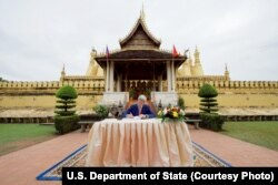 U.S. Secretary of State John Kerry signs the guest book after visiting the That Luang Stupa -- the most revered Buddhist temple in Laos -- following meetings with government leaders in Vientiane, Laos, Jan. 25, 2016.