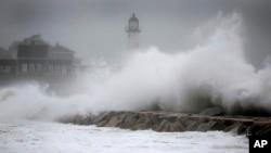Las olas chocan contra el faro Scituate, el viernes, en Scituate, Massachusetts.