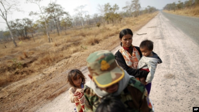 A Cambodian family is seen on an empty road as they flee the area near the 11th-century Preah Vihear temple on the border between Thailand and Cambodia, February 7, 2011.