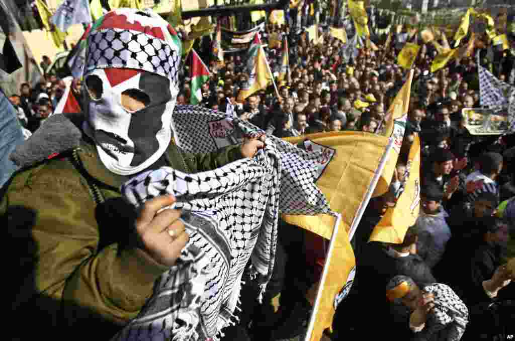 A masked Palestinian holds a traditional Arab headdress during Fatah anniversary celebration in the West Bank city of Nablus, January 3, 2013.