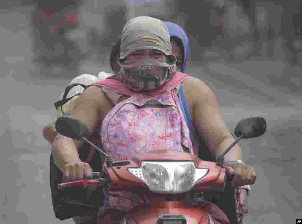 موتورسوار فیلیپینی و خانواده اش در پی فوران آتش فشان تال در جنوب این کشور، منطقه را ترک میکنند.