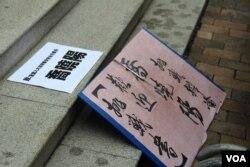 """邀请乔晓阳参加公开辩论的""""战书""""被放在中联办台阶上(美国之音海彦拍摄)"""