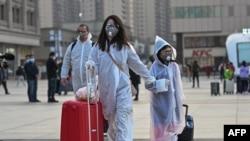 Люди в захисному одязі на залізничній станції в Ухані, 8 квітня 2020 року